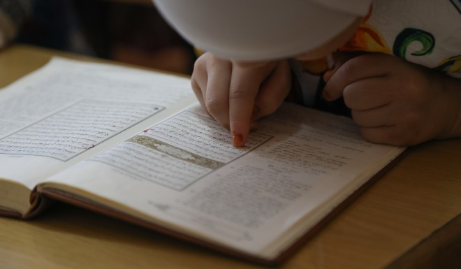 A girl reads the Koran in Uygur.