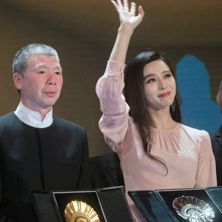Chinese director Feng Xiaogang holds up the Concha de Oro (Golden Shell)  award for