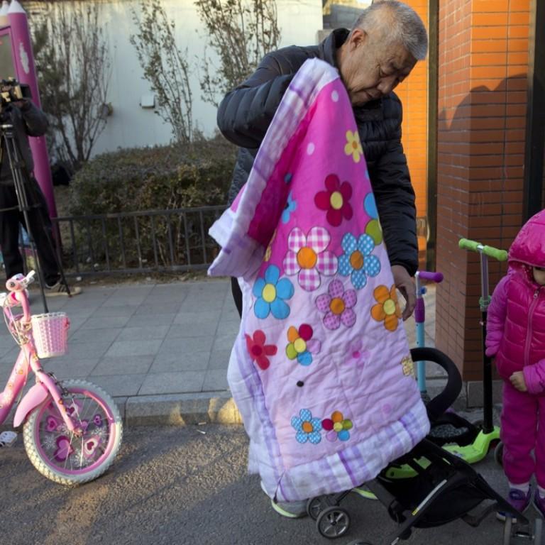 An elderly man escorts a child to the RYB Education New World kindergarten  in Beijing on