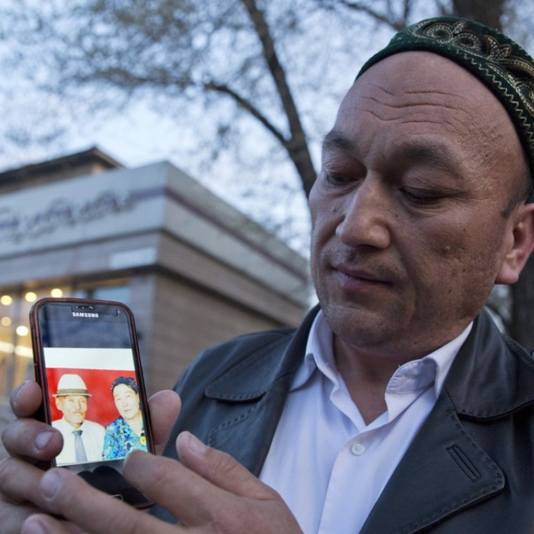 Omir Bekali holds up a mobile phone showing a photo of his parents whom he believes have been detained in China's western Xinjiang region. Photo: AP