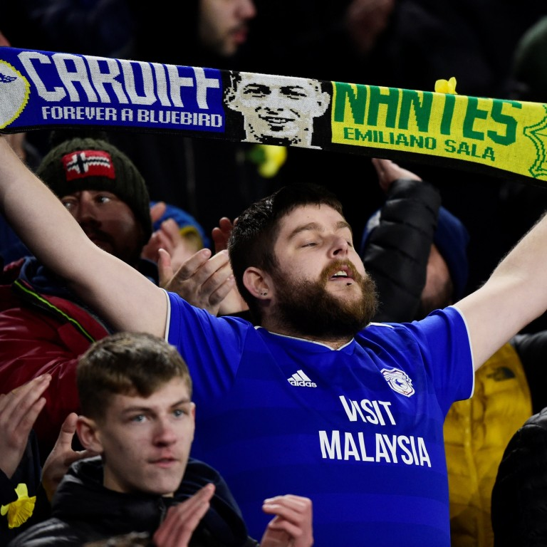 e9dbf3ef5 A Cardiff City fan holds up a scarf paying tribute to Emiliano Sala. Photo