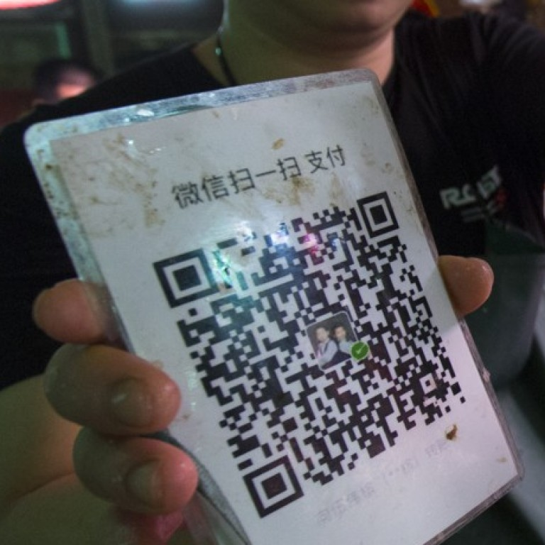 A fish vendor in China holding a QR code to accept mobile payments (Picture: May Tse)