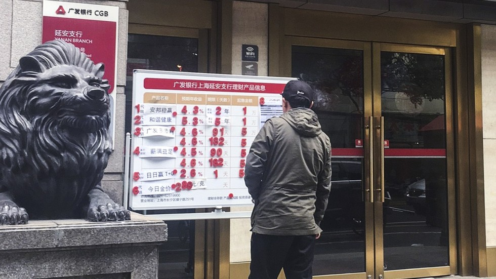 a passer by looks at the advertisement of a universal insurance policy and other wealth management products sold by anbang group at a china guangfa bank