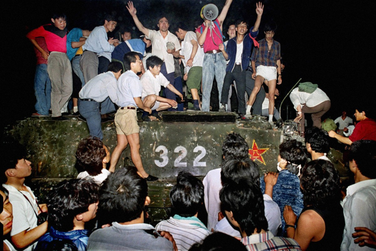 Protesters climb aboard an armoured personnel carrier in front of the locked gates leading to the Great Hall of the People.