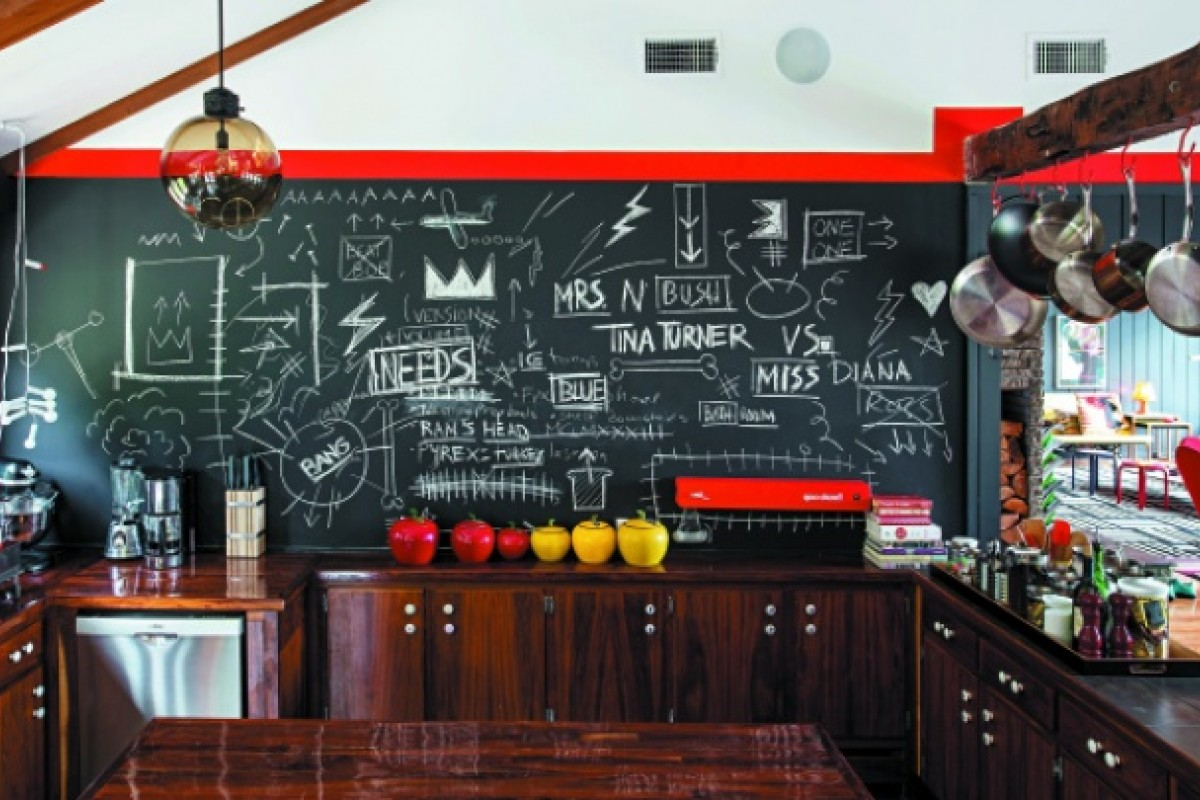 The brightly coloured kitchen has a huge blackboard with scribbles all over.