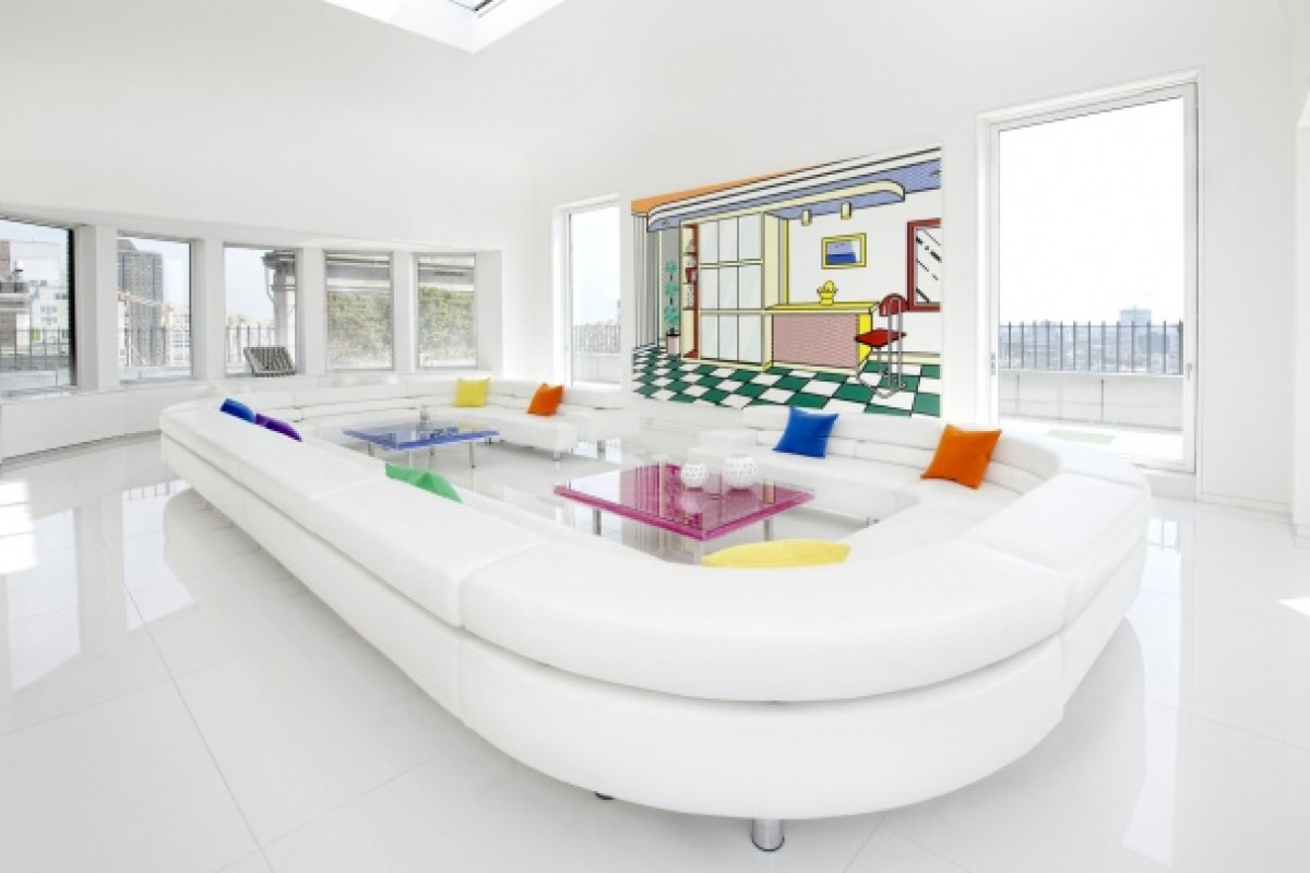 In the living room, the maxi white leather couch is juxtaposed with the bright and vivid colours of Rauschenberg and Lichtenstein paintings on the wall.