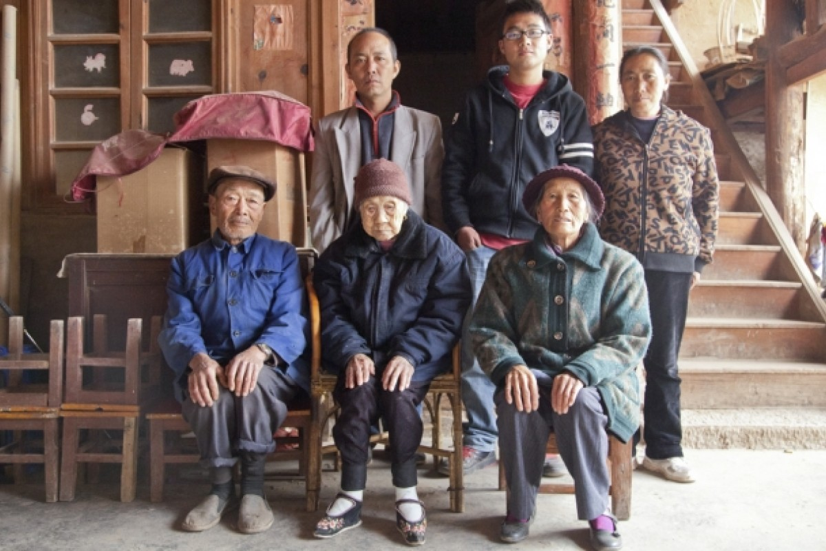 Yang (centre) with members of three other generations of her family, including her eldest son and the wife of her second son (both seated).