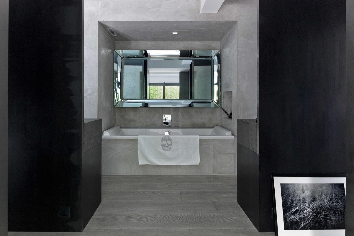 Master en-suite: The Duravit by Starck tub came from Depot (371 Lockhart Road, tel: 3106 6008), where the same model costs from HK$8,960 (150cm by 70cm) to HK$19,680 (two metres by one metre). The mirror (HK$25,000), also by Starck, came from Dentro (LG/F, Wilson House, 19 Wyndham Street, Central, tel: 3741 1351). To the left of the tub is the toilet and to the right the shower. Leaning against a wall in the dressing area is a photograph by Rob Lutter (roblutter.com).