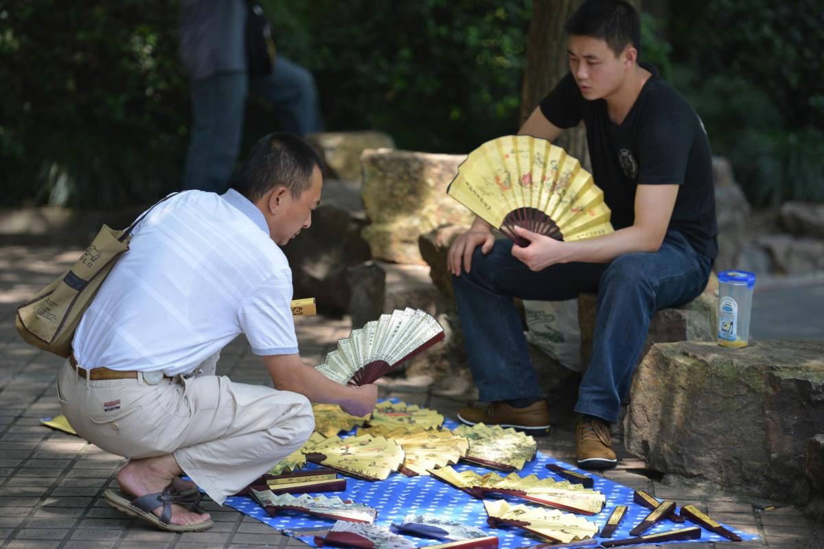 A fan vendor sets up shop on a Shanghai street in July.