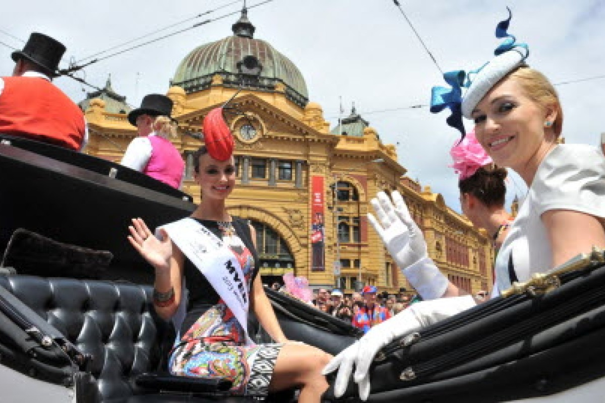 Fashions on the Fields contestants wave during the Melbourne Cup parade in Melbourne on Monday. Photo: EPA