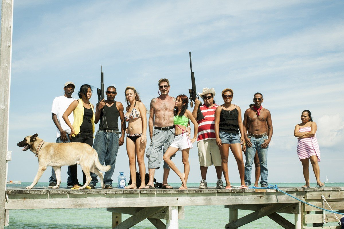 John McAfee (centre) with a retinue of bodyguards and young women, including Amy Emshwiller (fourth from left) and Sam Vanegas (embracing McAfee), in Belize. Photos: Brian Finke; AFP