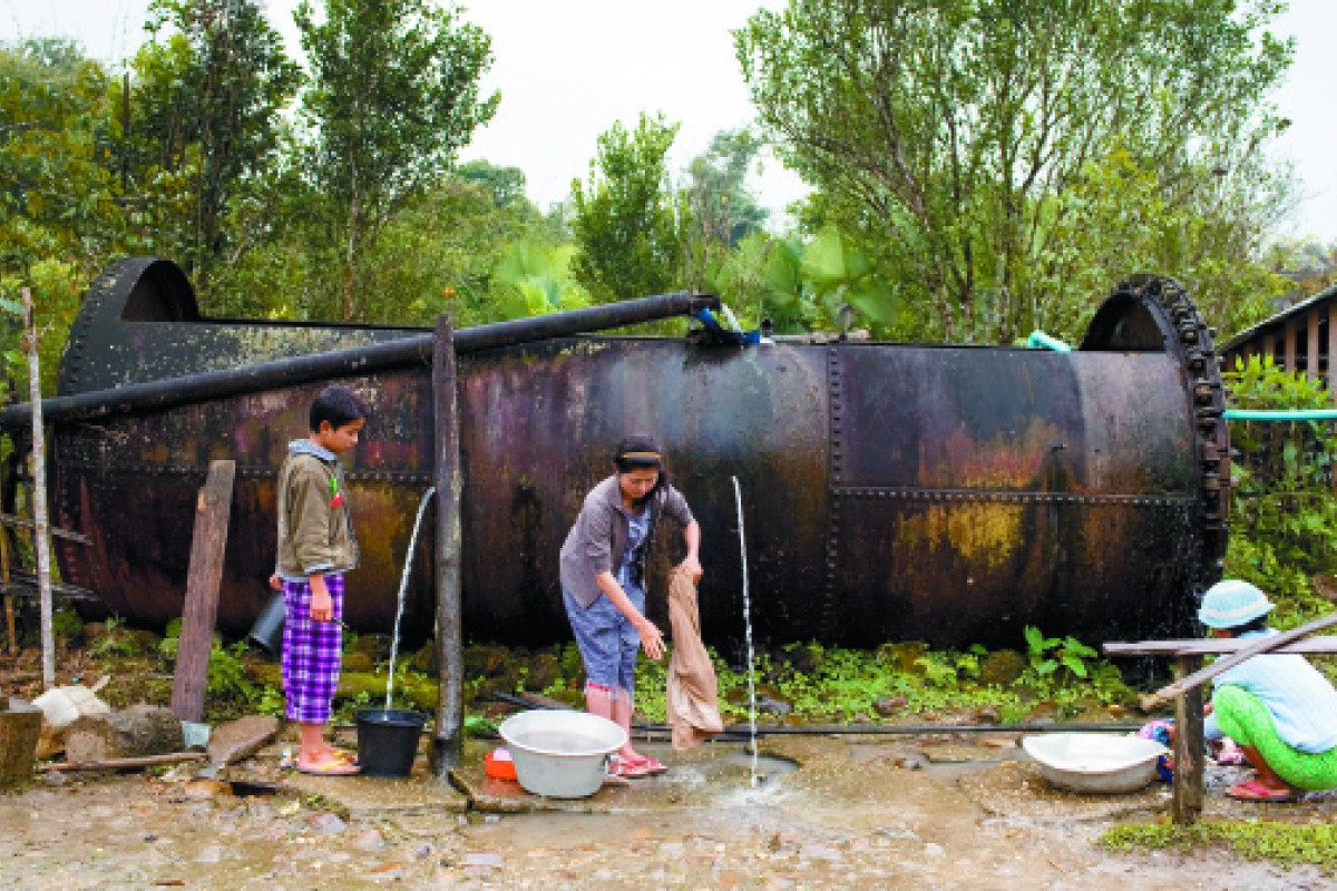 Villagers use a gas tank from the second world war as a water container on a section of the Stilwell Road in Kachin state.