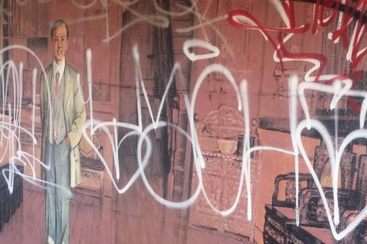Graffiti on the mural1905: Man in a Suit, in Chinatown, Vancouver.