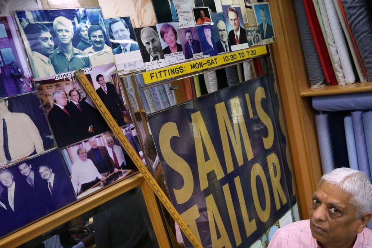 Sam's Tailor boss Manu Melwani points to a photo he has of the late David Bowie visiting the shop. Picture: Jonathan Wong
