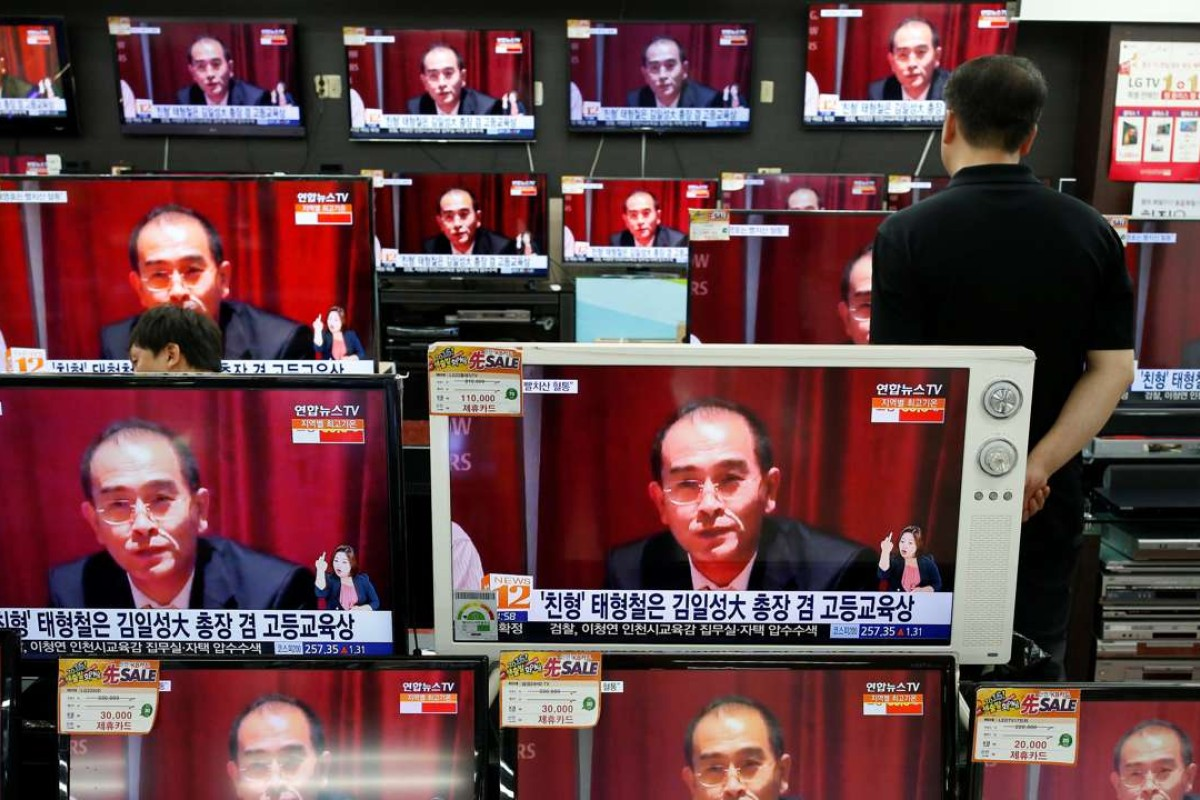 A sales assistant watches TV sets broadcasting a news report on Thae Yong Ho, North Korea's deputy ambassador in London, who has defected with his family to South Korea. Photo: Reuters