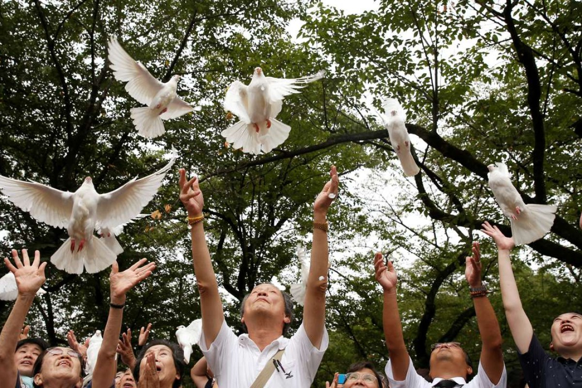 People release doves as a symbol of peace at the Yasukuni Shrine in Tokyo, in August 2016, to mark the anniversary of the end of the second world war. Photo: Reuters