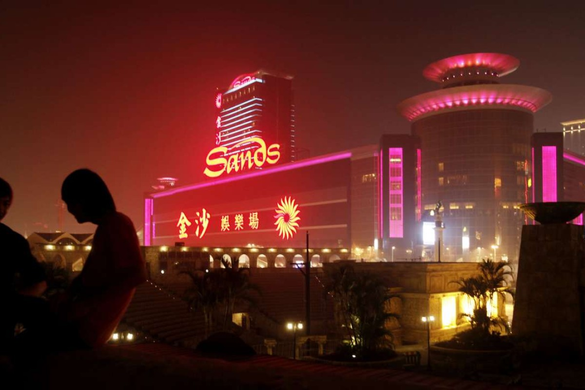 Two men sit in front of the Sands Casino in Macau. Photo: AP
