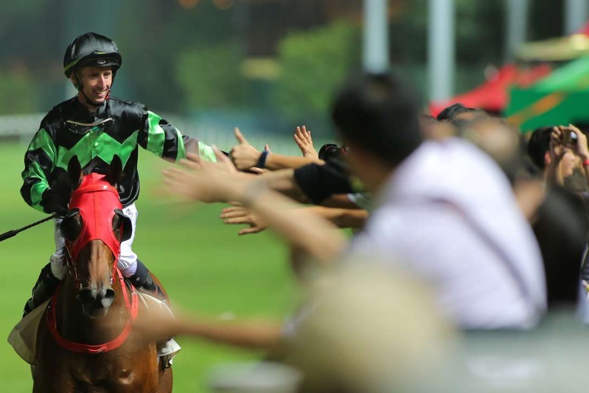 A beaming Nash Rawiller high fives fans after winning the final race of the night on Inventor. Photos: Kenneth Chan