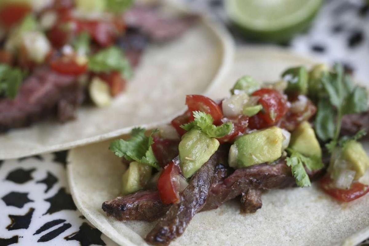 Carne asada tacos with avocado and tomato salsa. Photography: Jonathan Wong