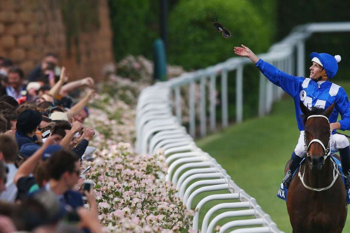 Jockey Hugh Bowman celebrates Winx's Cox Plate win with the crowd. Photo: Getty Images