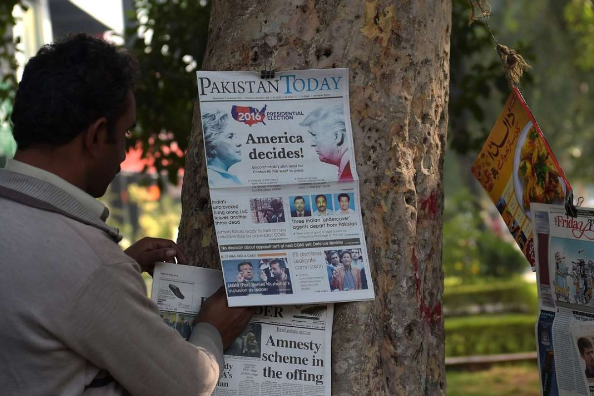 A Pakistani vendor arranges morning newspapers featuring front-page news of the US presidential election at a roadside news stand in Islamabad. Photo: AFP