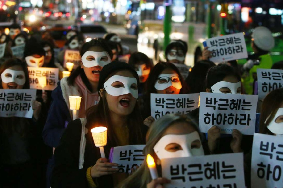 South Korean university students march with candlelight and placards demanding President Park Geun-Hye step down during a protest in Seoul this week. Photo: EPA
