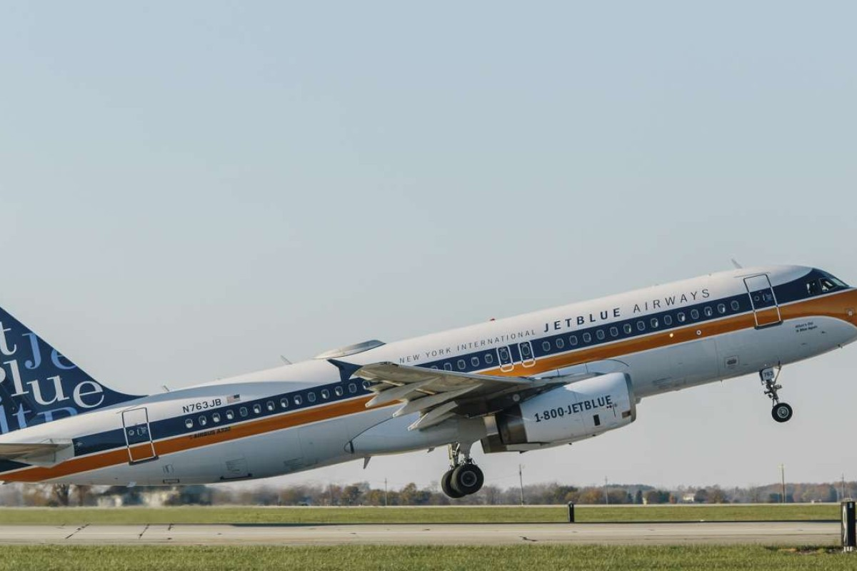 The retro-livery JetBlue Airbus A320 takes off.