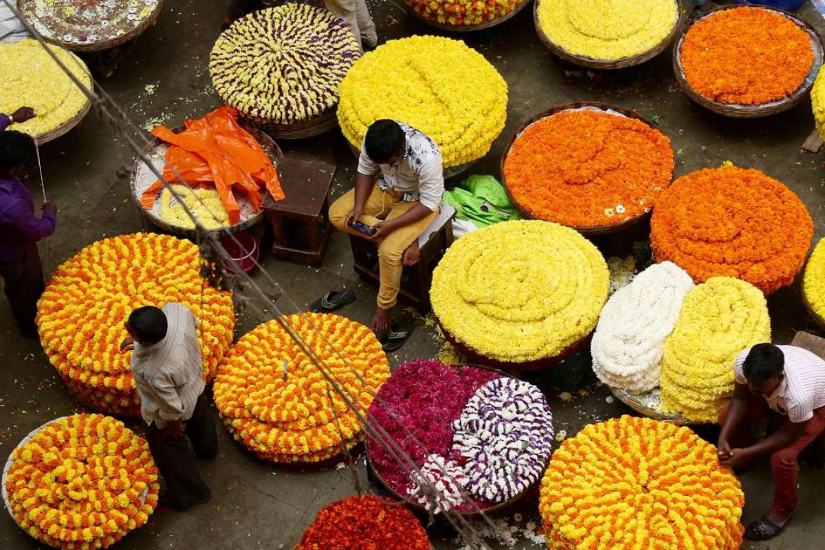 Indian flower vendors wait for customers at a market in Bangalore. Indian businesses have been hit hard by the lack of currency notes in the wake of the government's decision to ban high denomination notes. Photo: EPA