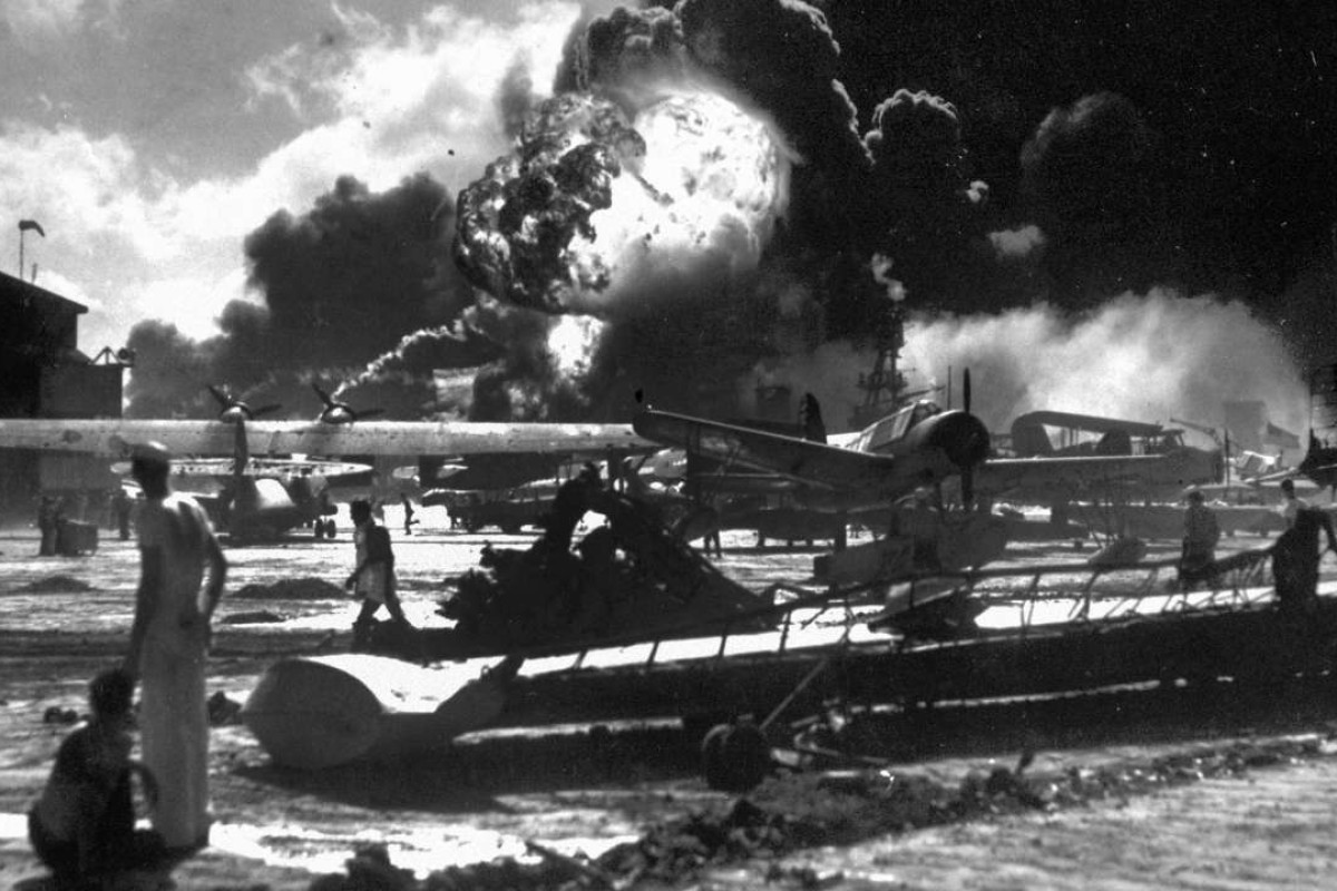 Sailors stand among wrecked airplanes at Ford Island Naval Air Station as they watch the explosion of the USS Shaw, background, during the Japanese surprise attack on Pearl Harbour, Hawaii. Photo: AP