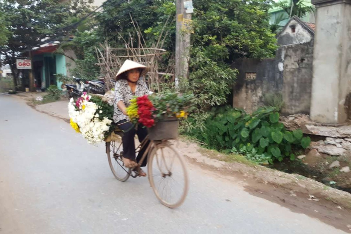 A vendor carries flowers to the market on her bicycle. Photo: Karim Raslan