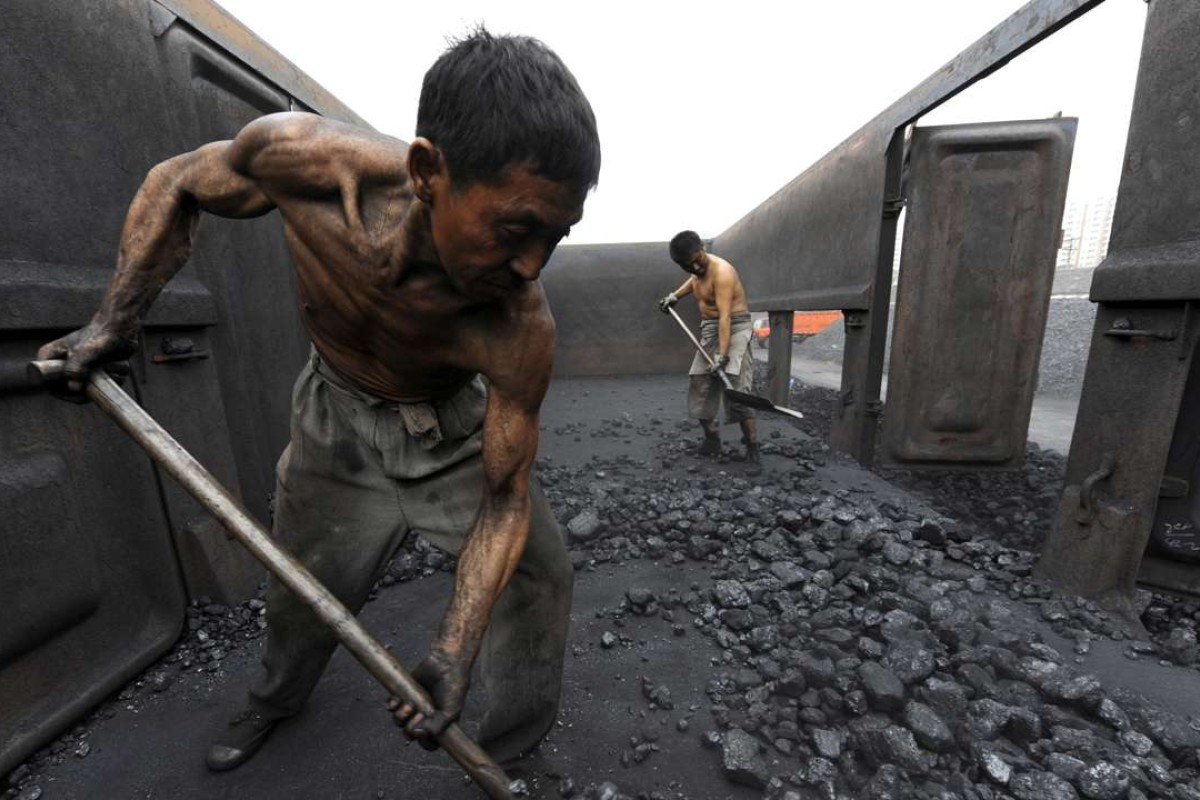 Workers unload coal at a storage site along a railway station in Hefei, Anhui province, China. Photo: Reuters