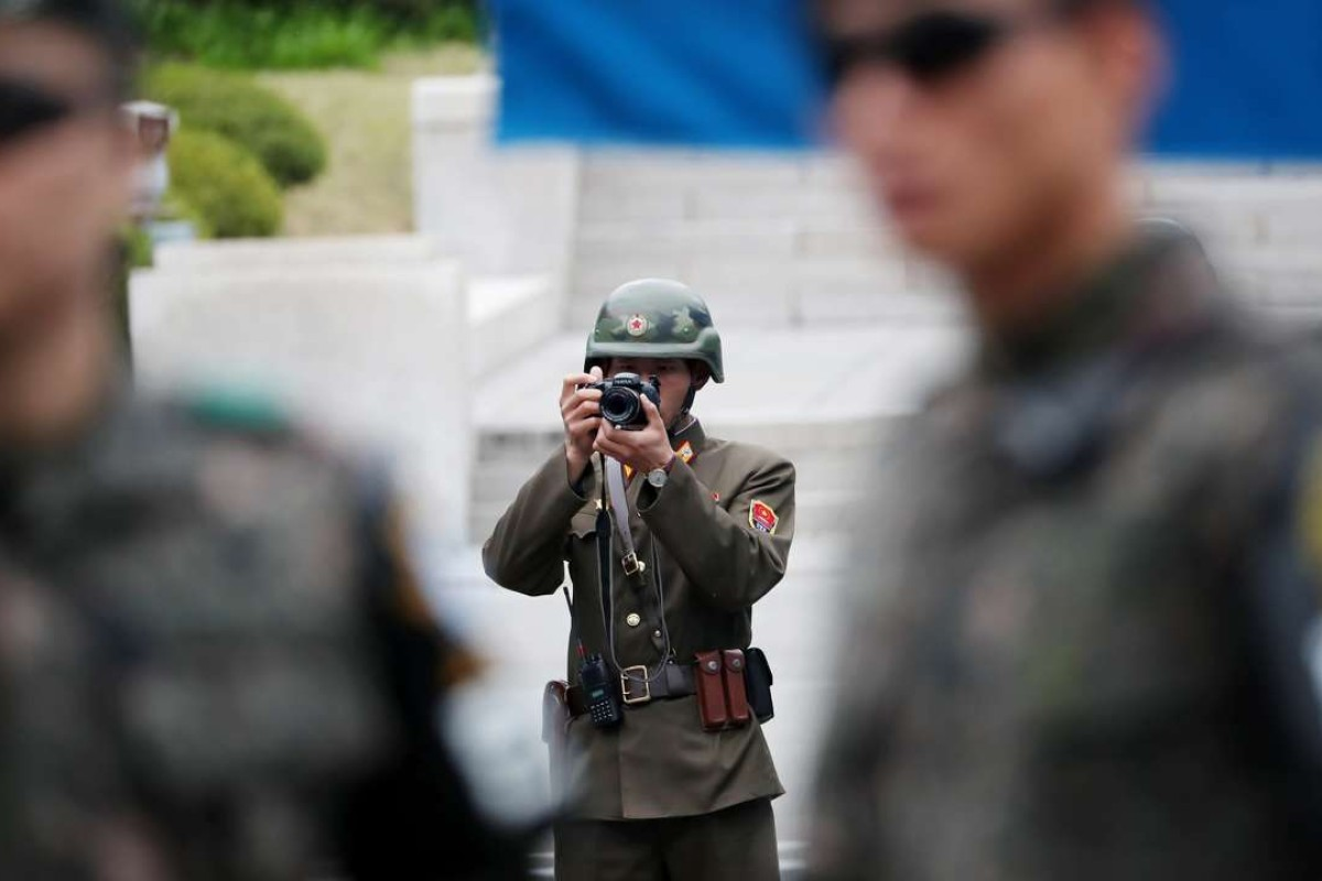 A North Korean soldier takes a photograph as South Korean soldiers stand guard at the truce village of Panmunjom in the Demilitarized Zone in Paju, South Korea. Photo: Bloomberg