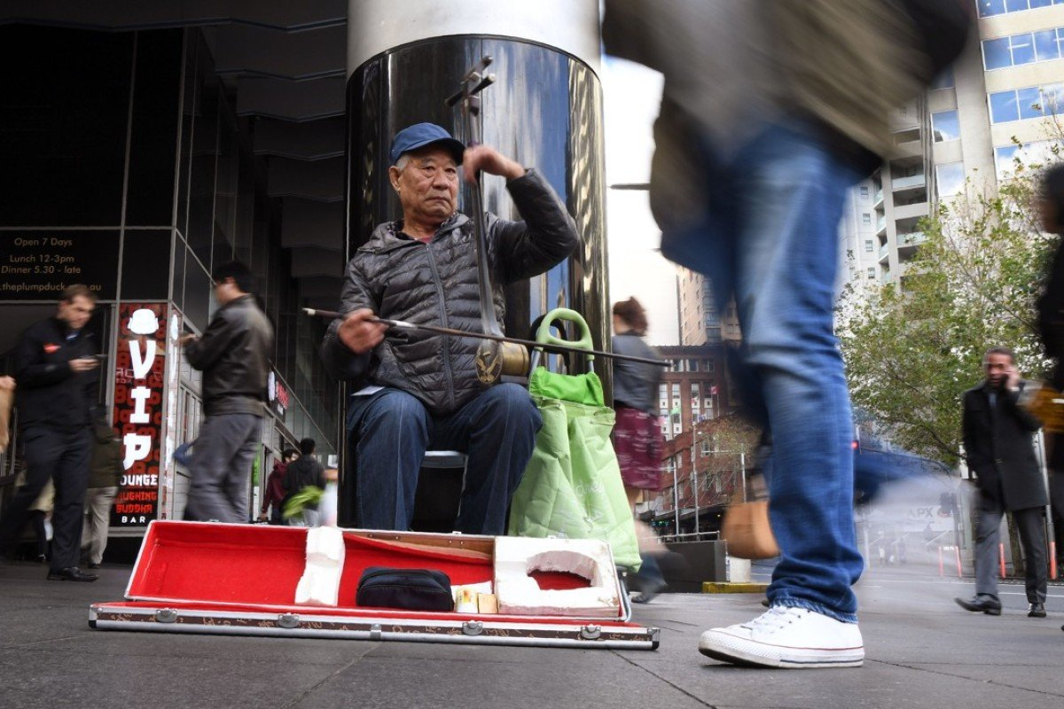 """A busker plays a traditional Chinese fiddle, or """"erhu"""", along a street in Sydney. For the first time Asian migration has outstripped European, and Mandarin is now the second-most spoken language after English. Photo: AFP"""