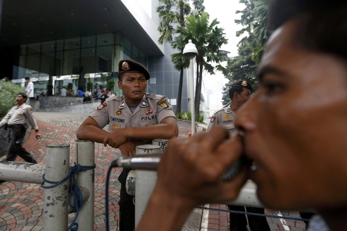 A policeman on guard as a protester shouts slogans outside the Corruption Eradication Commission building in Jakarta. Photo: Reuters