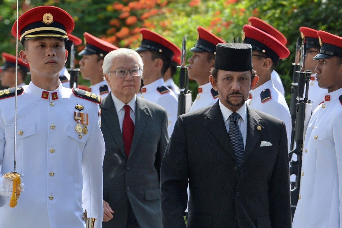 Sultan of Brunei Hassanal Bolkiah, front right, is accompanied by Singapore's President Tony Tan Keng Yam as they inspect an honour guard during his welcoming ceremony at the Istana presidential palace in Singapore. Photo: AFP