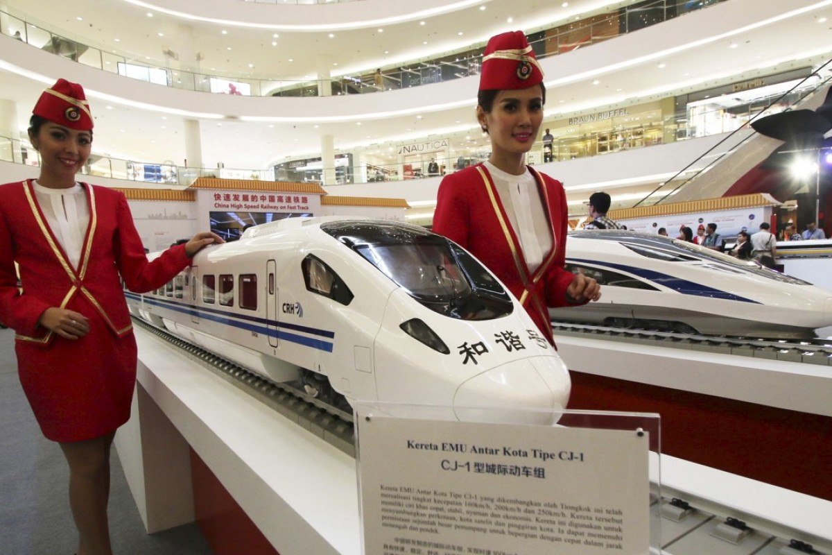 Attendants pose for a photo beside the models of a high-speed train during the China High Speed Railway on Fast Track exhibition in Jakarta, Indonesia. China is competing for a contract to build a high-speed railway connecting Singapore and Malaysia. Photo: Reuters