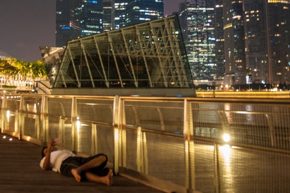 A migrant worker rests on the promenade near Singapore's Marina Bay Sands casino. A number of migrant workers have gambled their way into debt. Photo: Justin Kor