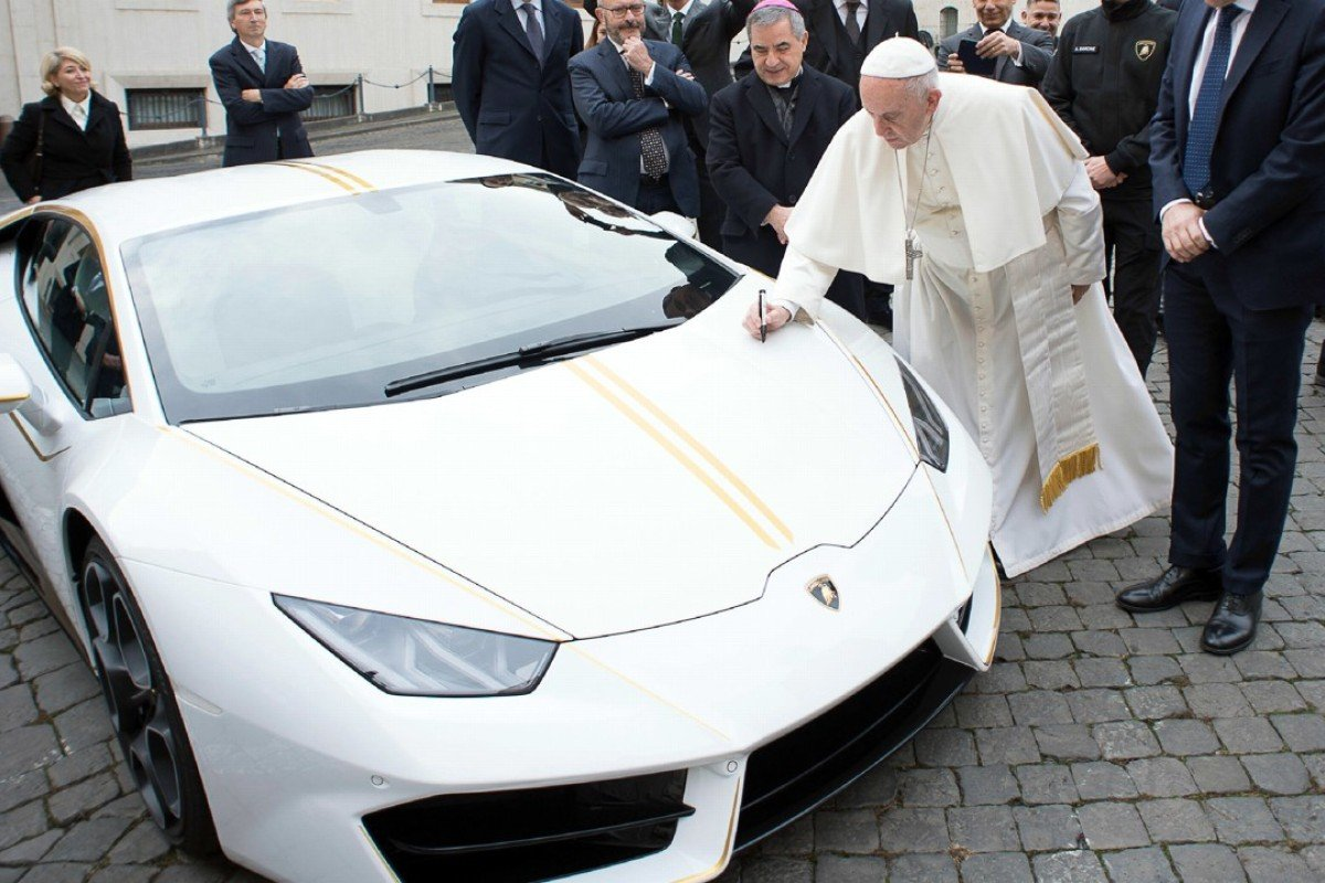 Pope Francis writes on the bonnet of the Lamborghini, given to him by the Italian luxury sports carmaker, which he will auction in aid of Christian communities in Iraq. Photo: AP