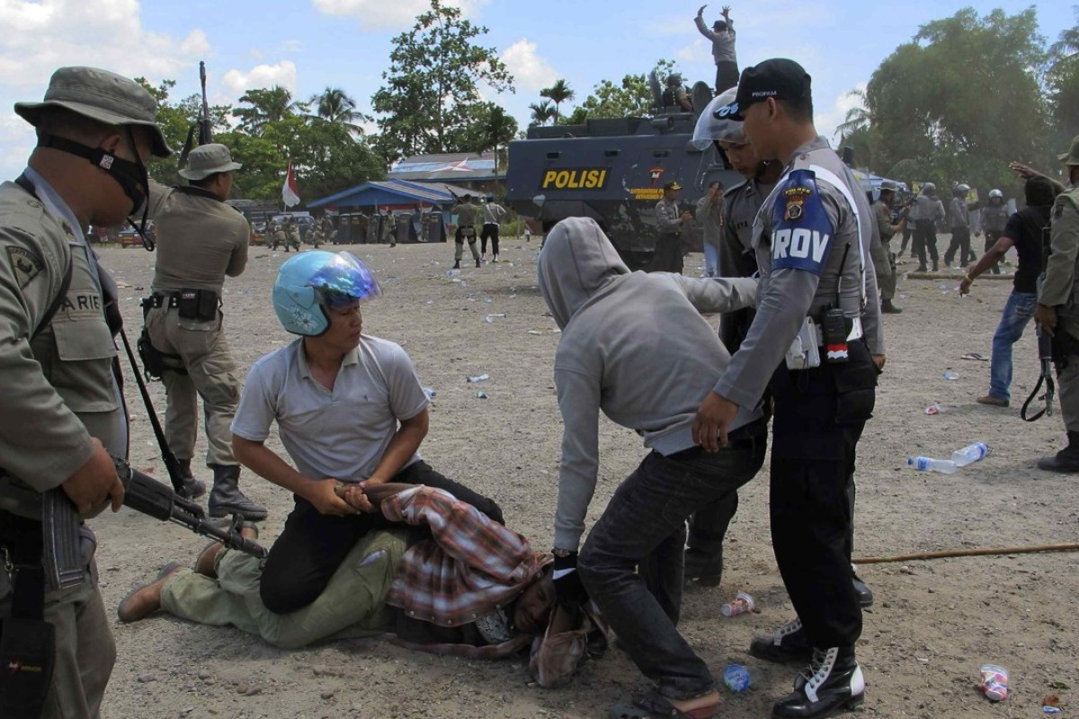 Police arrest a man in Timika after dispersing hundreds of West Papuans attending a ceremony to commemorate the 50th anniversary of West Papua's independence from Dutch rule. Photo: Reuters