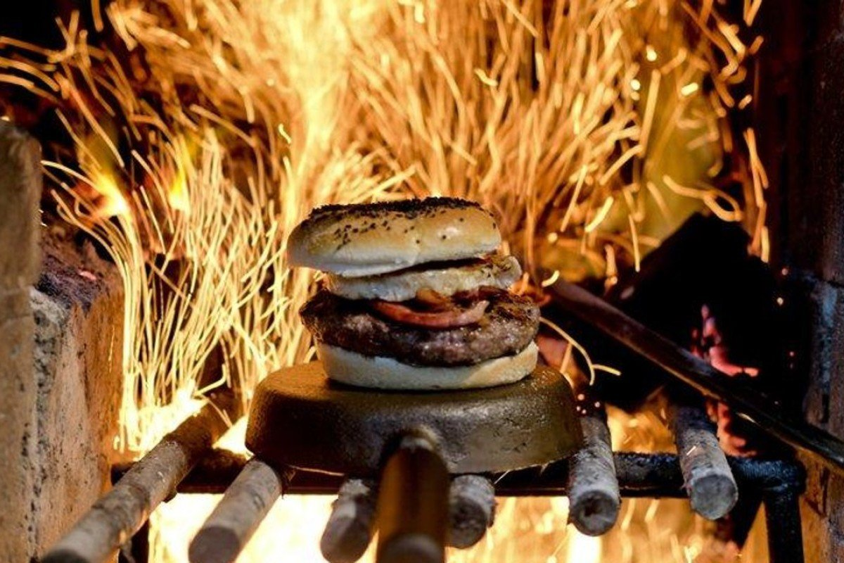 A hamburger is cooked by wood-fuelled fire at Kon Kon restaurant in Buenos Aires, Argentina. Photo: AP