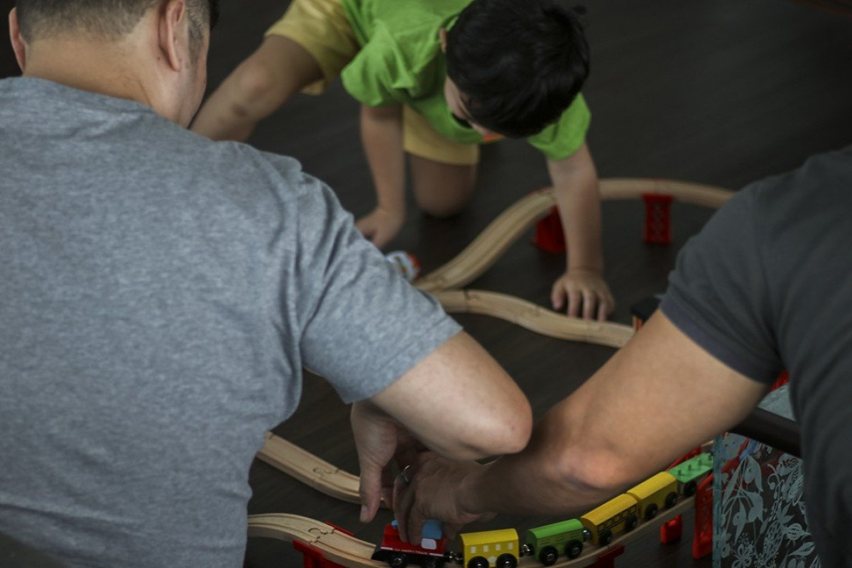 Shawn, left, James, right, and their son Noel, centre, play with a toy train they got Noel for Christmas. The two men are fighting for the right to keep in Singapore their son, the biological son of James and a surrogate mother in the United States. Photo: Don Wong