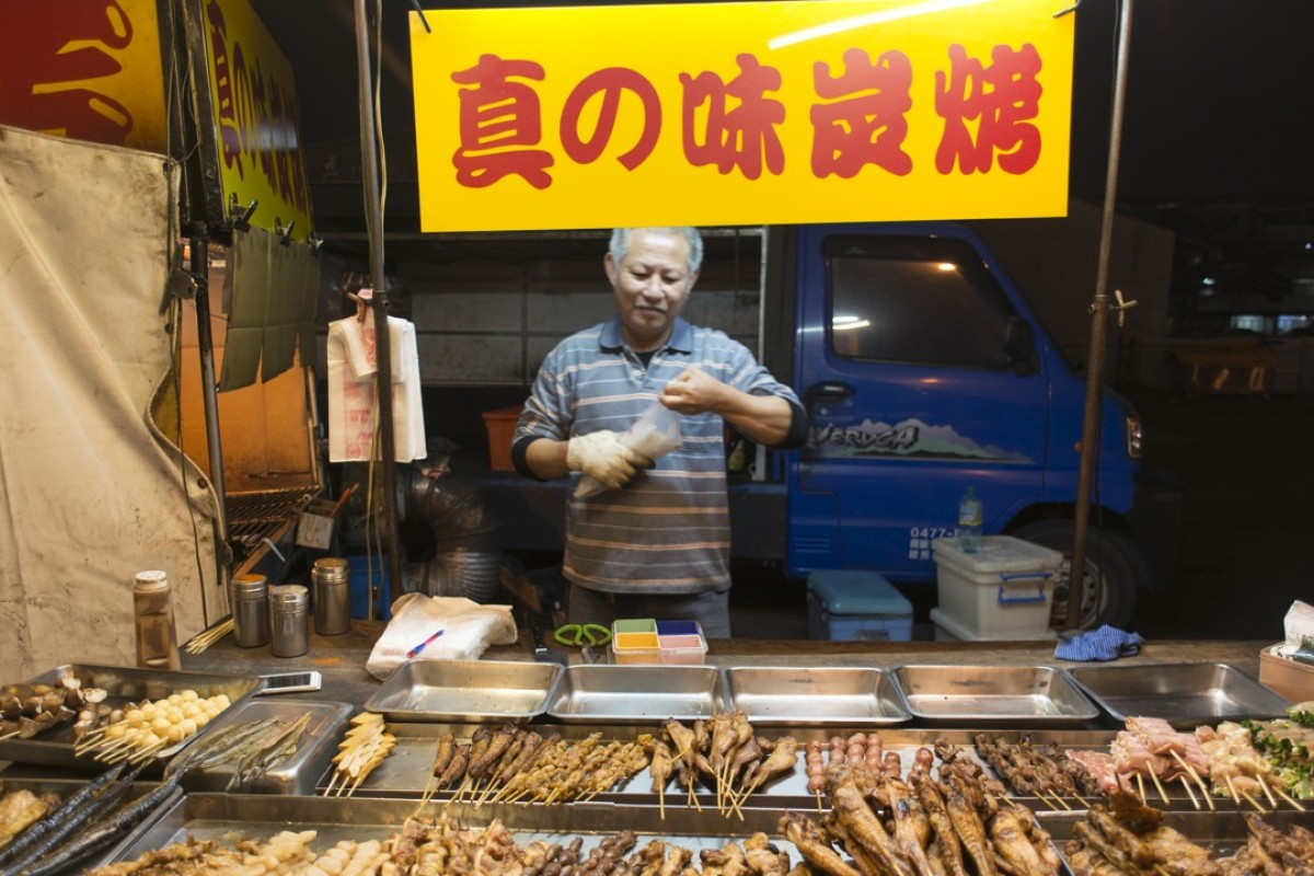 A vendor sells grilled meats on a skewer at a night market in Tainan, Taiwan. Picture: Antony Dickson