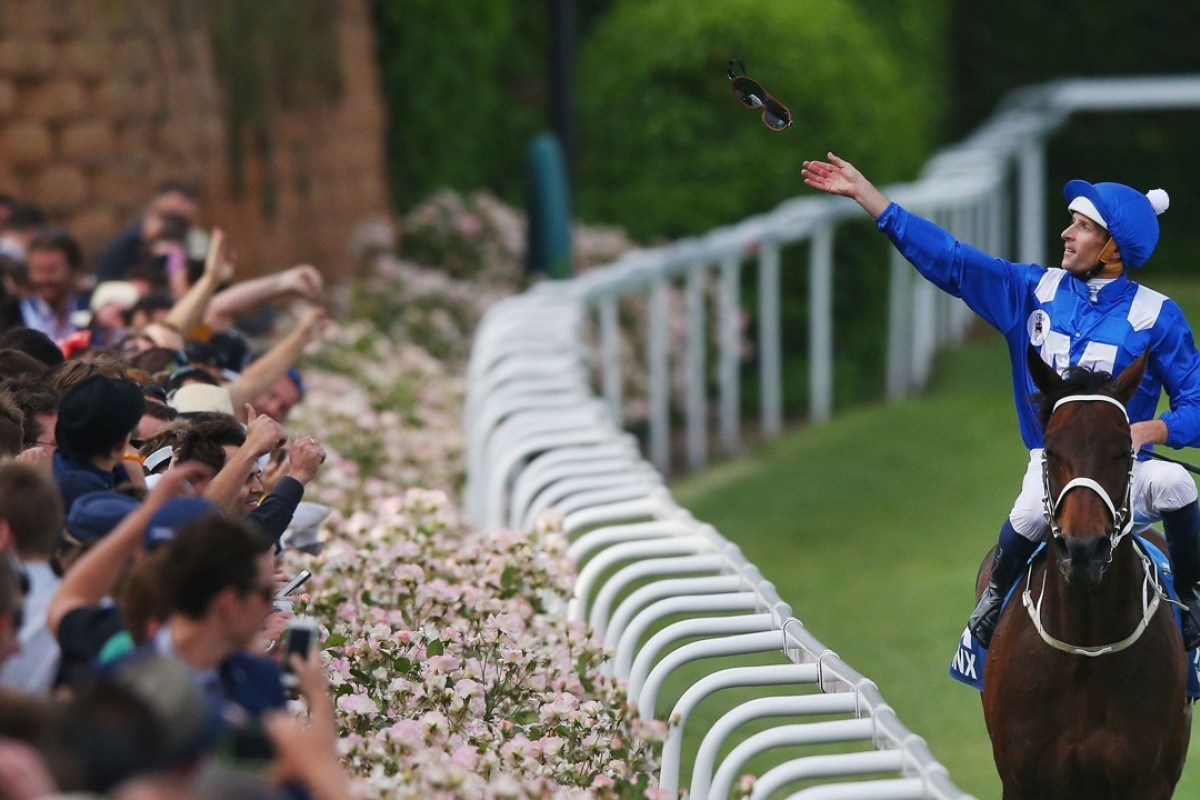 Hugh Bowman throws his goggles into the crowd after winning the Cox Plate with Winx. Photo: Michael Dodge/Getty Images