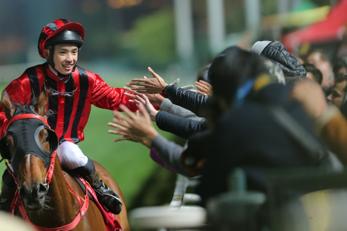 Jack Wong celebrates with the fans after winning aboard Dinozzo on Wednesday night. Photos: Kenneth Chan