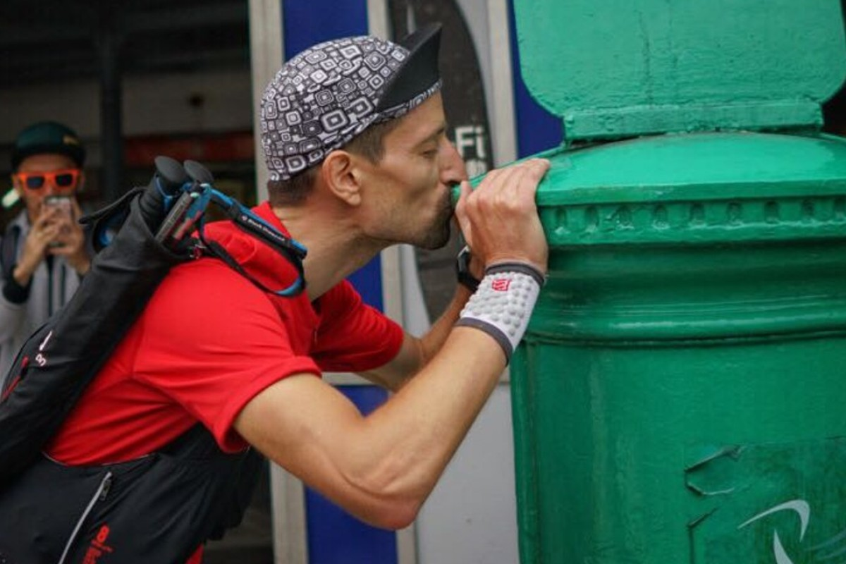 Salomon Wettstein kisses the postbox in Mui Wo after becoming the first 'finisher' in this year's Four Trails Ultra Challenge. Photos: Lloyd Belcher Visuals
