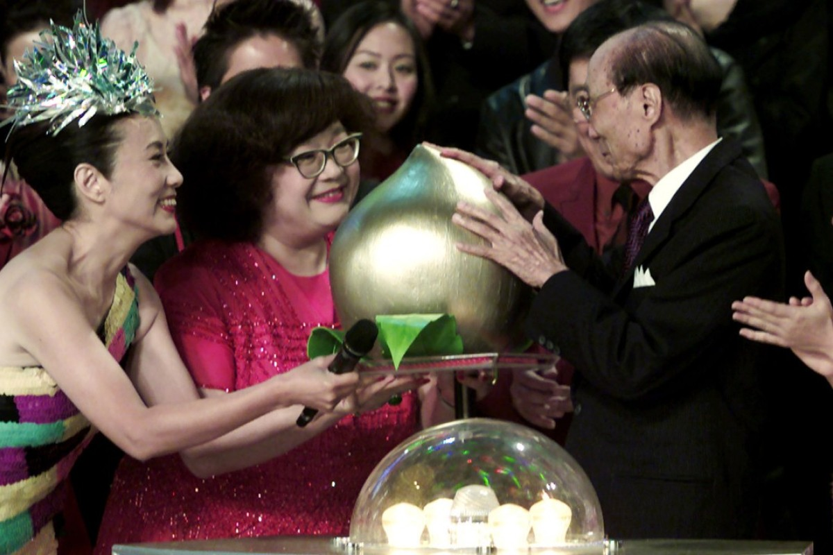 Late chairman of Television Broadcasts Limited (TVB) Run Run Shaw (right), receives a birthday present of a golden peach from Shum (second left) and Liza Wang Ming-chun (left) during the 'TVB 34th Anniversary Special' in 2001.
