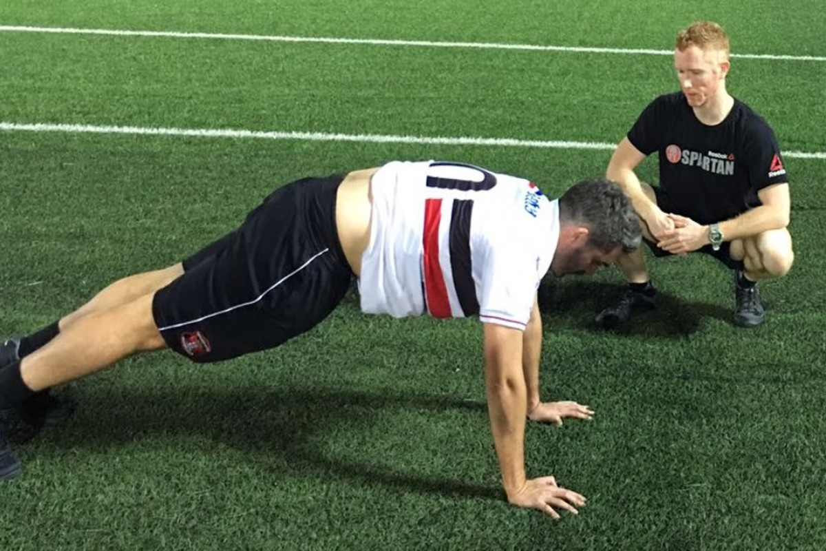 Andrew Power instructs Post reporter Jonathan White on the burpee. Photos: Handout