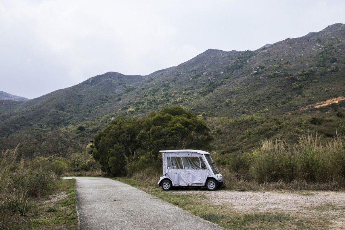 A golf cart sits parked next to a trail on a hilly side at Discovery Bay. Photo: Justin Chin/Bloomberg