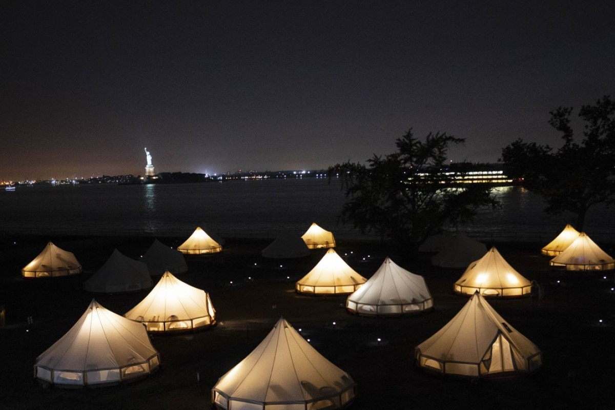 Glowing Journey Tents at night in the foreground with the Statue of Liberty and Staten Island Ferry behind. Photo: David Gray/Bloomberg