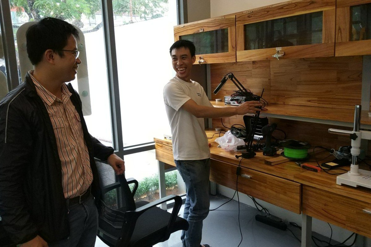 Nguyen Ba Hoi, left, shares a light moment with a colleague at Maker Innovation Space. Photo: Mai Duong